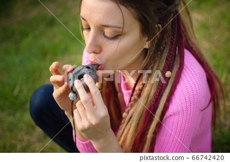 Portrait of young female shaman in pink knitted sweater playing on ceramic ocarina in the forest during autumn or spring. Relaxing tranquil scene, traditional music concepts 66742420