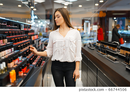 Woman takes lipstick from shelf in cosmetics store 66744506