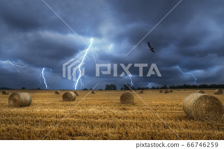 Hay bales on field during a lightning storm. Dark 66746259
