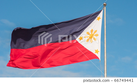 Flying bicolor flag of the Philippines with central golden sun representing the provinces and stars the islands. 66749441