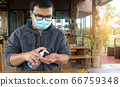 Thailand Man wearing medical face mask using hand 66759348