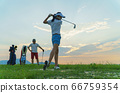 Couple in action of playing golf together. 66759354