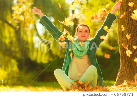 Happy woman throwing autumn leaves in park 66768771
