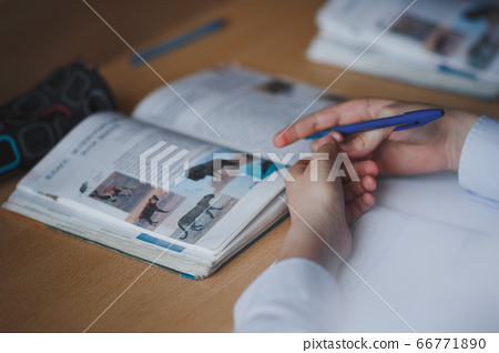 On the school desk with a textbook and hands of the student. 66771890
