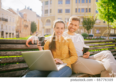 Woman with laptop and man drinking coffee 66776389