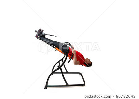 Man doing exercise on inversion table for his back 66782045