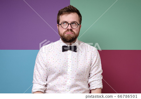 Offended, upset, bearded man in round glasses pouted his lips and looks up thoughtfully. 66786501