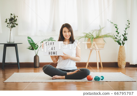 Woman holding stay at home sign. Self isolation 66795707
