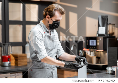 Salesman in protective wear in the cafe during a pandemic 66798242