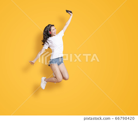young woman jumping while listening to music on 66798420
