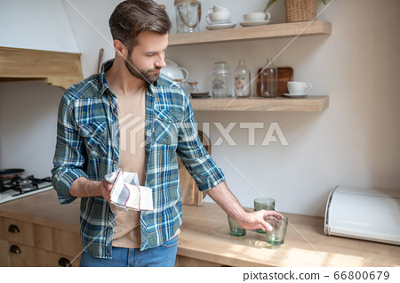 Young man in a checkered shirt putting the clean glass on the table 66800679