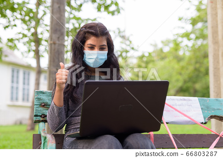 Young Indian woman with mask video calling and giving thumbs up while sitting with distance on park 66803287