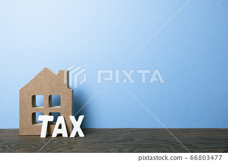 House model with tax on wooden table with blue background. Mortgage or property tax concept 66803477