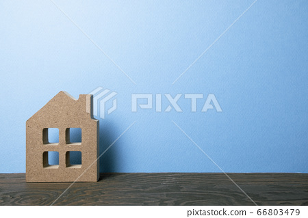 House model on wooden table with blue background. Real estate concept 66803479