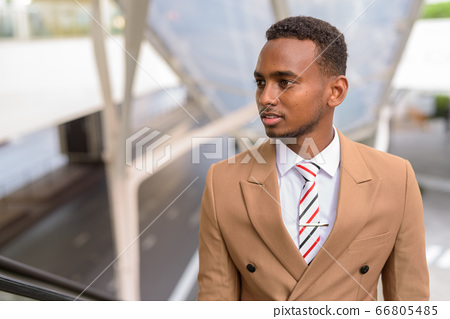 Young handsome African businessman thinking while going up the escalator in the city 66805485