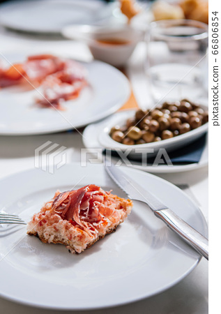 Sliced Jamon Spanish ham on crispy bread on white plate 66806854