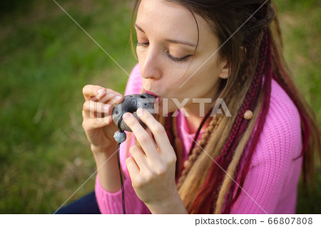 Portrait of young female shaman in pink knitted sweater playing on ceramic ocarina in the forest during autumn or spring. Relaxing tranquil scene, traditional music concepts 66807808