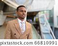 Happy young handsome African businessman thinking at footbridge in the city 66810991