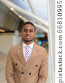 Happy young handsome African businessman smiling at the footbridge 66810995