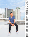 Full body shot of young handsome multi ethnic man with sunglasses sitting against view of the city 66810997