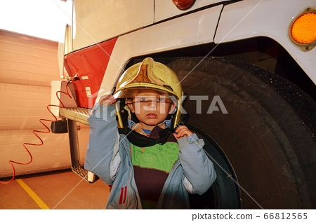 Little boy acting like a fireman. Boy standing next a real fireman car. Happy adorable child boy with fireman hat standingnext red fire truck. Dreaming of future profession. Fire safety, life 66812565