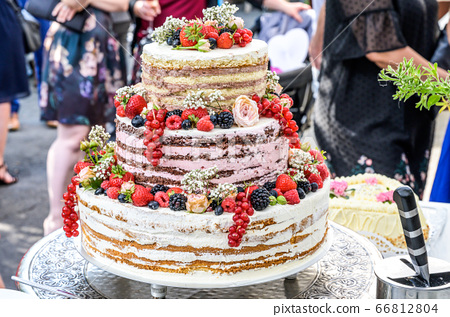 beautiful delicious Wedding cake in many tiers with fresh wild berries and fruits 66812804