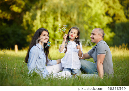 happy family with child girl blow soap bubbles 66838549