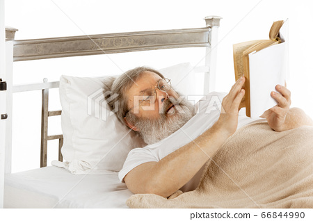 Elderly old man recovering in a hospital bed isolated on white 66844990