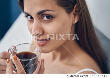 Attractive young woman drinking tea in bedroom 66848315