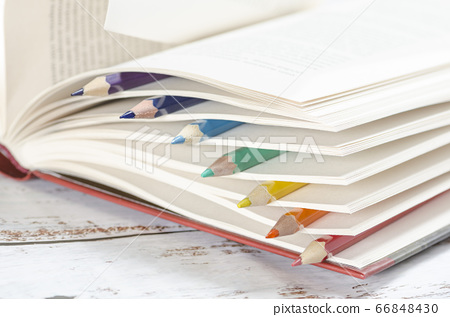 Colored pencils between pages of a book 66848430