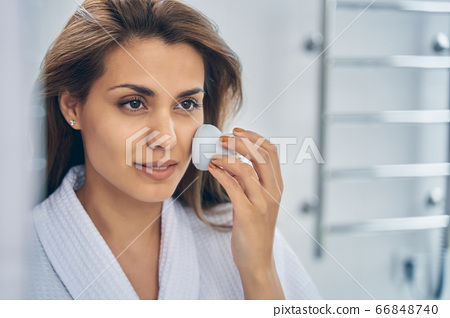 Attractive young woman using facial cleansing brush 66848740