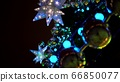 Close up of large yellow balls on blurry luminous multi-pointed blue stars background and decoration on Christmas tree square at Christmas market square 66850077