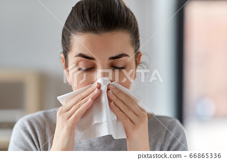 sick woman blowing nose in paper tissue at home 66865336