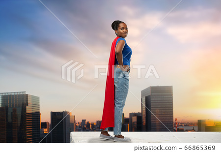 happy african american woman in red superhero cape 66865369