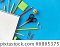 notebook and school supplies on blue background 66865375