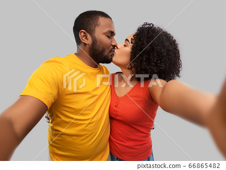 african american couple taking selfie and kissing 66865482