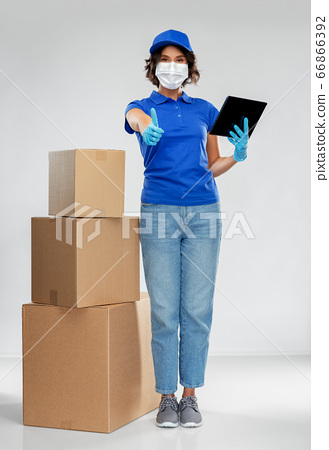 delivery woman in mask with boxes and tablet pc 66866392