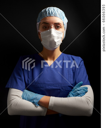 female doctor or nurse in goggles and face mask 66866393