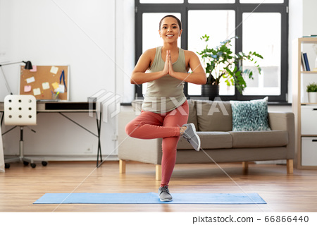 african american woman doing yoga pose at home 66866440