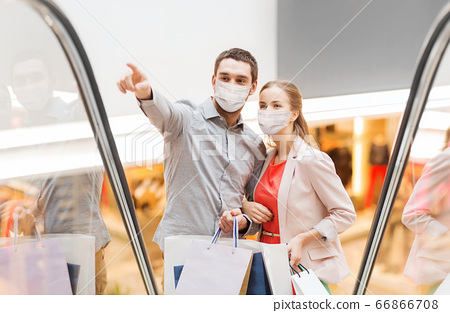 happy young couple with shopping bags in mall 66866708