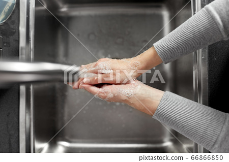 woman washing hands with soap in kitchen 66866850