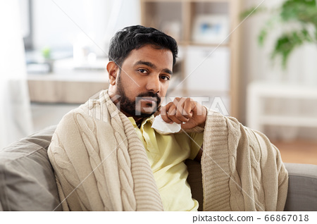 sick man in blanket with paper tissue at home 66867018