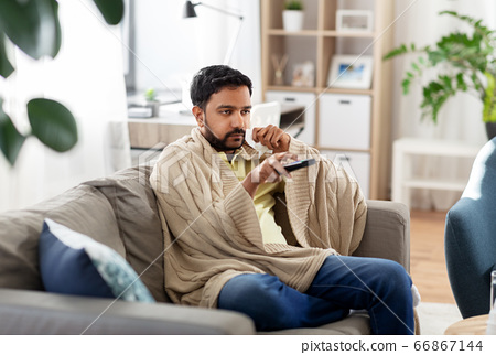 sick man with paper tissue and tv remote at home 66867144