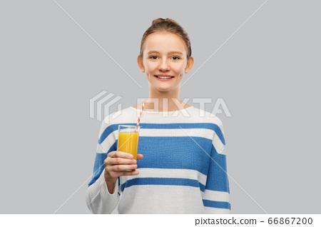 smiling teenage girl holding glass of orange juice 66867200
