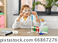 girl with magnifier and beaker at home laboratory 66867276