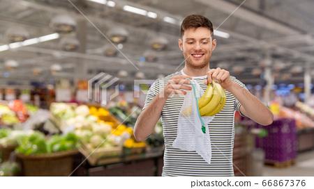 smiling man putting bananas into reusable net bag 66867376