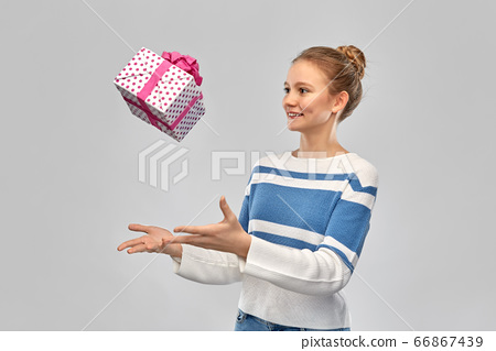 smiling teenage girl in pullover with gift box 66867439