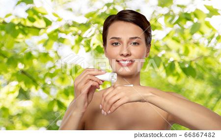 woman applying moisturizing cream to her hand 66867482
