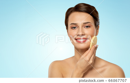 young woman cleaning face with exfoliating sponge 66867707