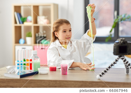 girl with slime and camera video blogging at home 66867946